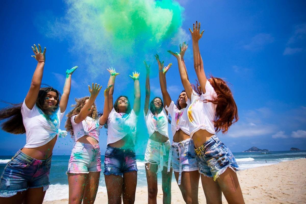 meninas jogando pó colorido pro céu.