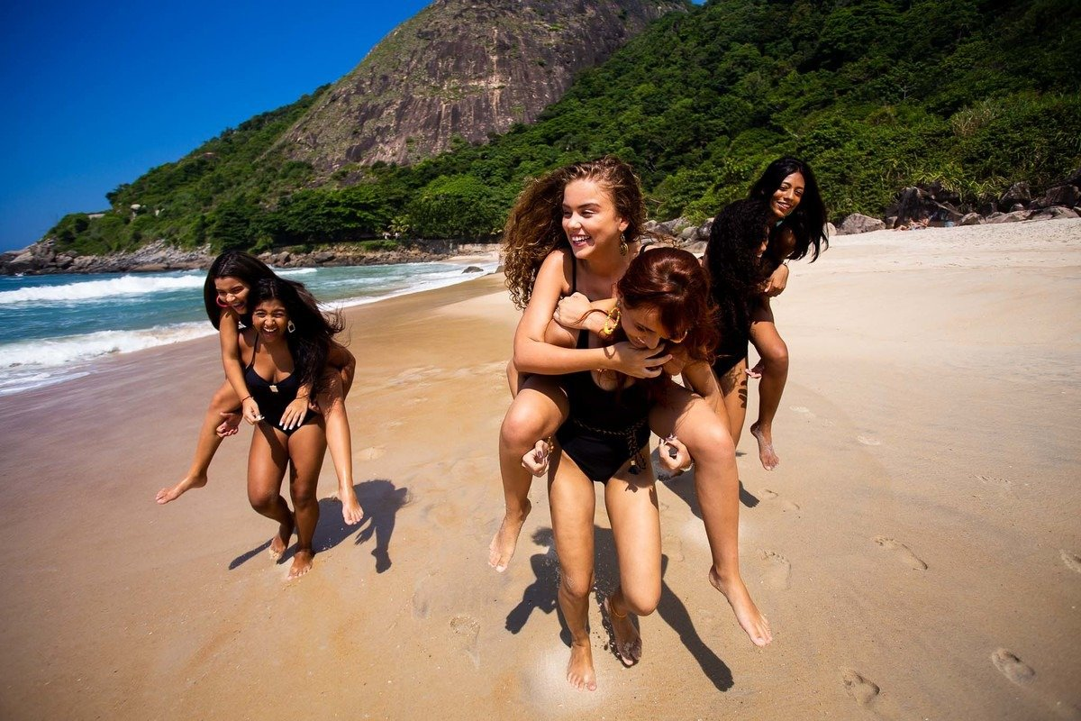 amigas apostando corrida de carcunda na areia da praia.