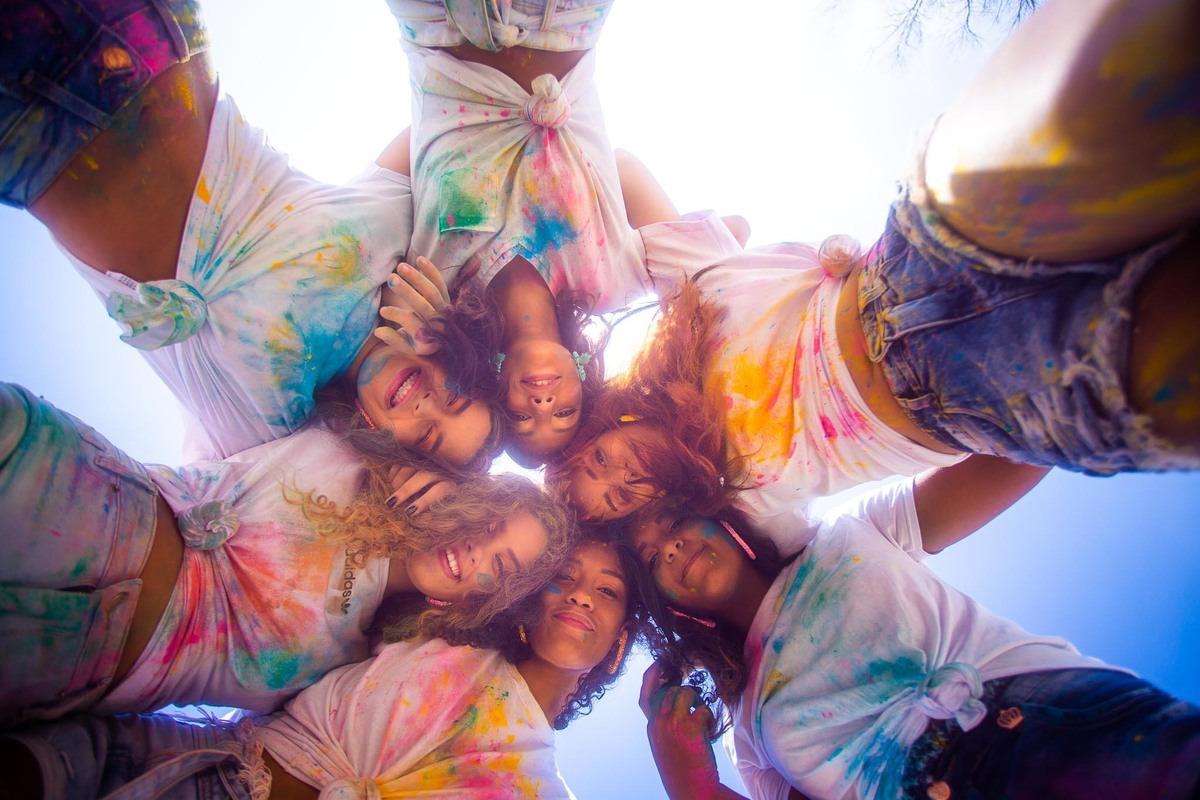 grupo de 6 meninas abraçadas e com roupas manchadas posando pra foto.