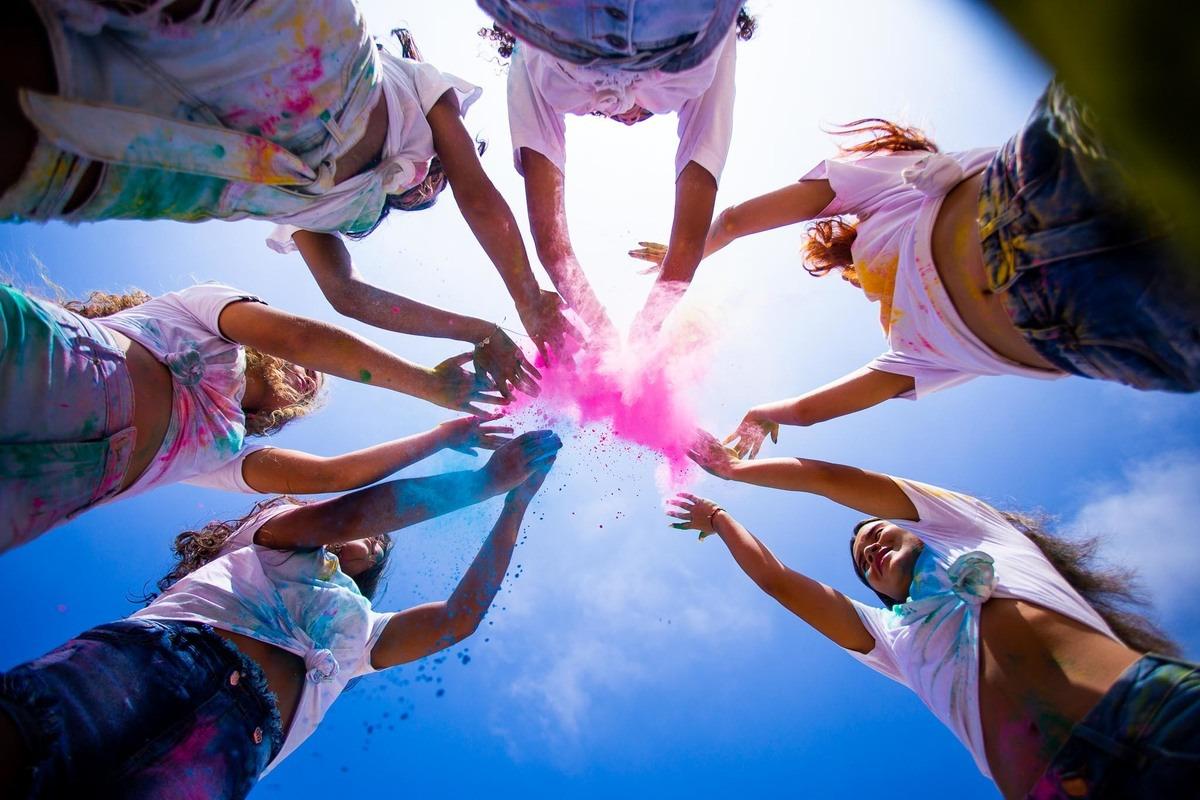 grupo de amigas jogando pó colorido pro alto.
