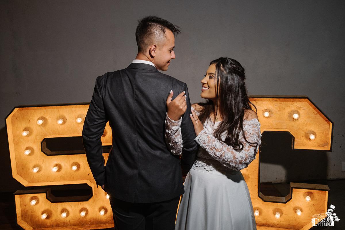 foto de casal com letreiro grande iluminado, casamento Boho