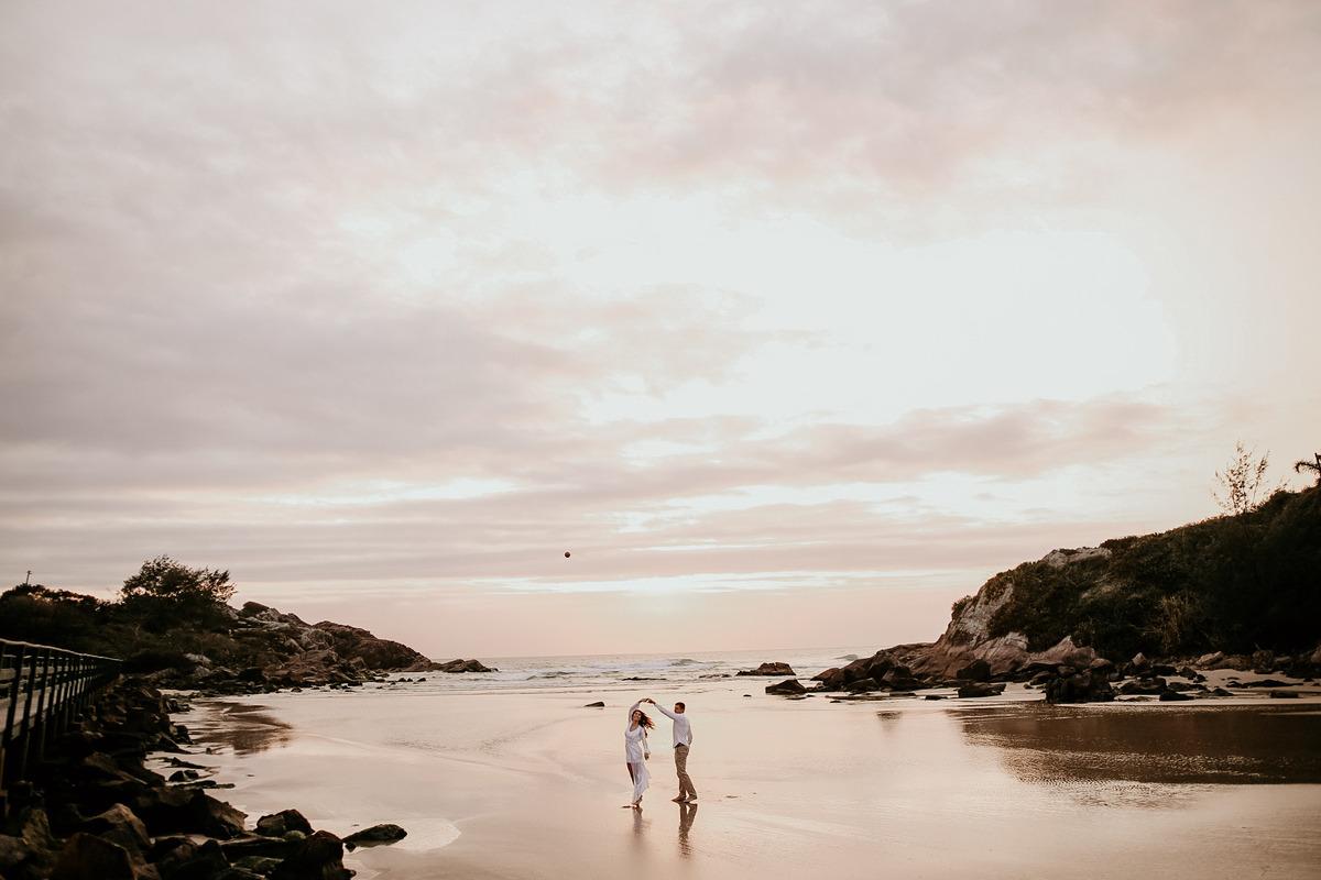 casal na areia da praia nascer do sol