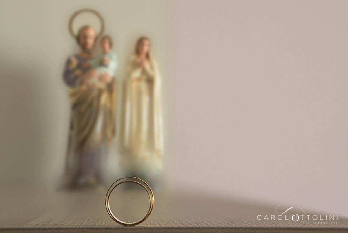 imagem de alianças de casamento com imagens de santo antônio e nossa senhora ao fundo