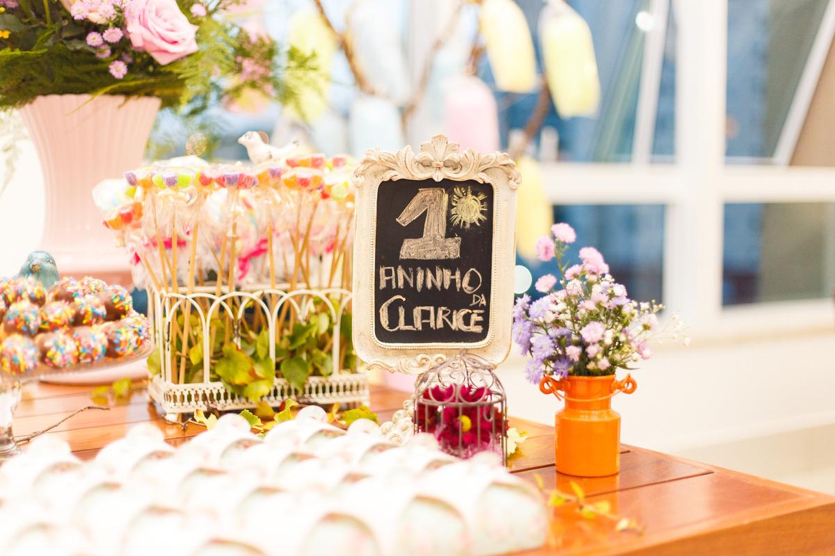 Detalhes da mesa do bolo de um aniversário do tema fazendinha, com alguns galões e flores.