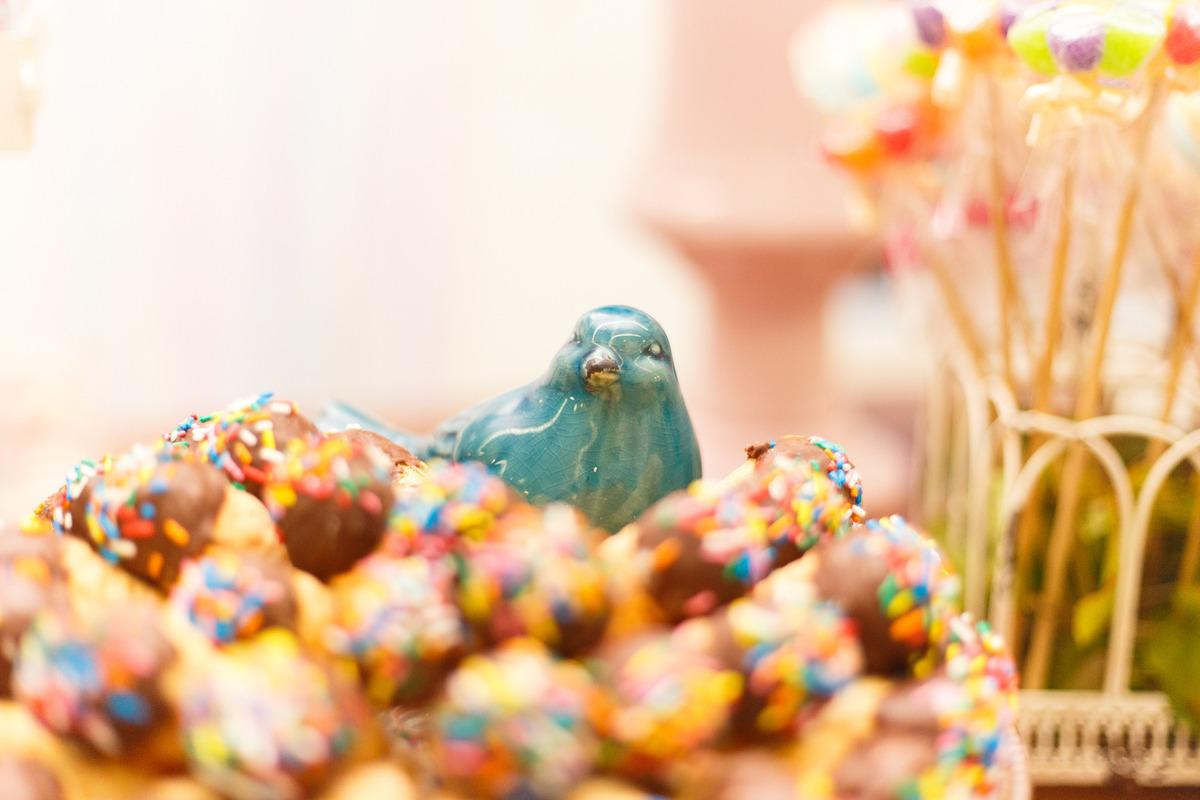 Foto de detalhe da mesa do bolo de um aniversário no tema fazendinha, com um passarinho de porcelana no meio dos doces.