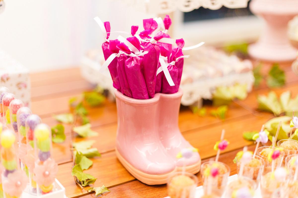 Detalhe de uma mesa do bolo em aniversário infantil com tema fazendinha, detalhe de uma bota tipo galocha.
