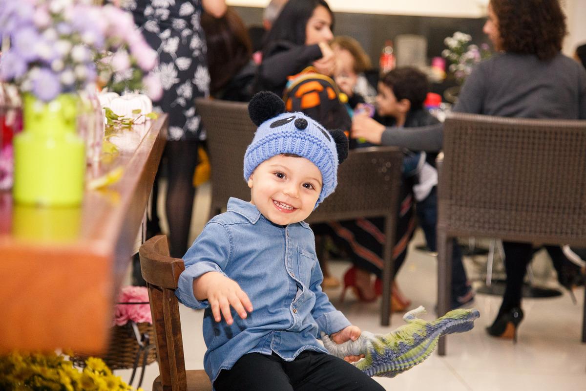 Criança sentada em uma cadeirinha em frente à mesa do bolo sorrindo, com um dinossauro na mão e um gorrinho de ursinho na cabeça.