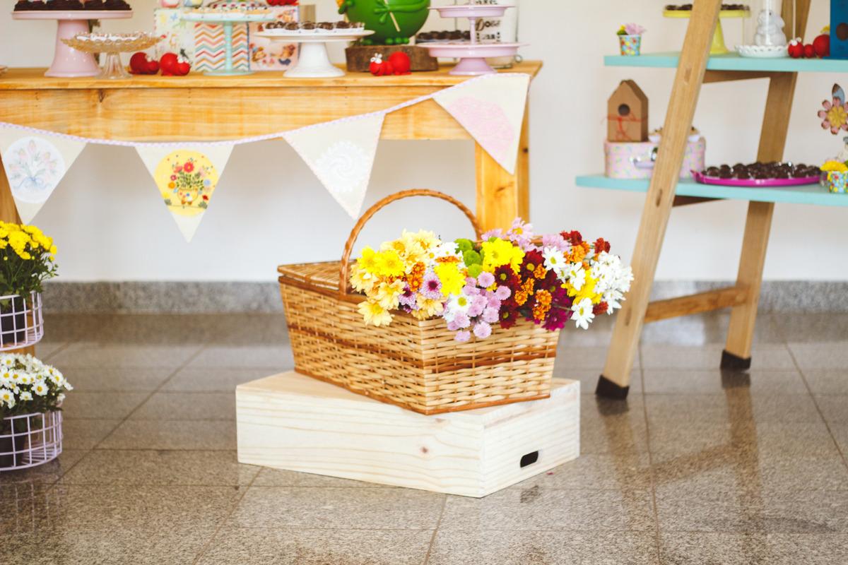 Detalhes da decoração de aniversário infantil no tema jardim, com uma cesta de flores em cima de um caixote de madeira.