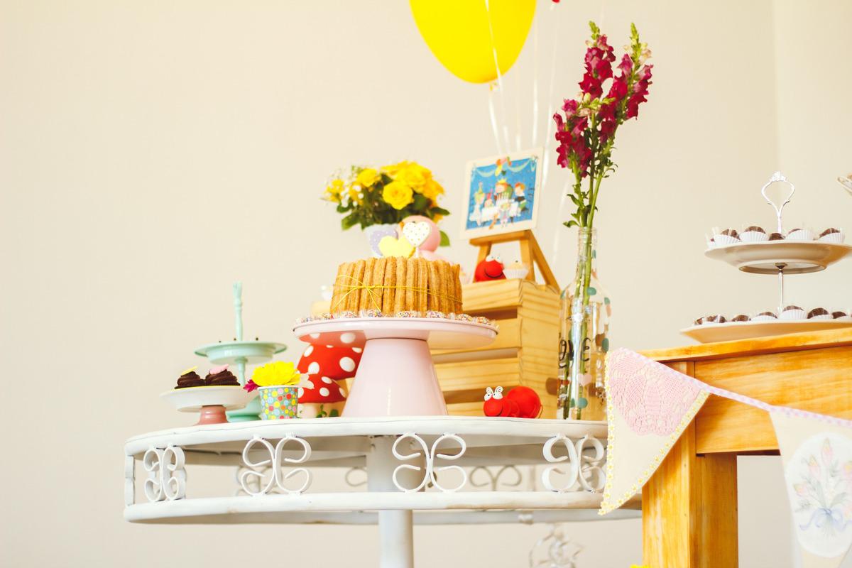 Detalhes da mesa do bolo de um aniversário infantil no tema jardim, com bolo de churros e cogumelos e formigas de biscuit.