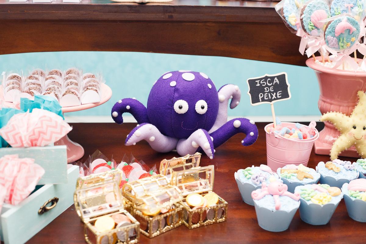 Detalhe da mesa do bolo de aniversário infantil no tema fundo do mar, com um polvo de pelúcia e outros detalhes.