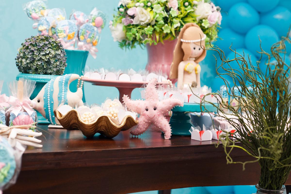 Detalhes da mesa do bolo de aniversário infantil no tema fundo do mar, com peixe, sereia e estrela do mar de pelúcia.