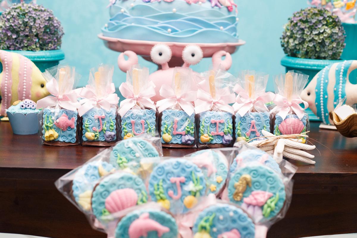 Detalhe da mesa do bolo de aniversário infantil no tema fundo do mar, com doces personalizados.