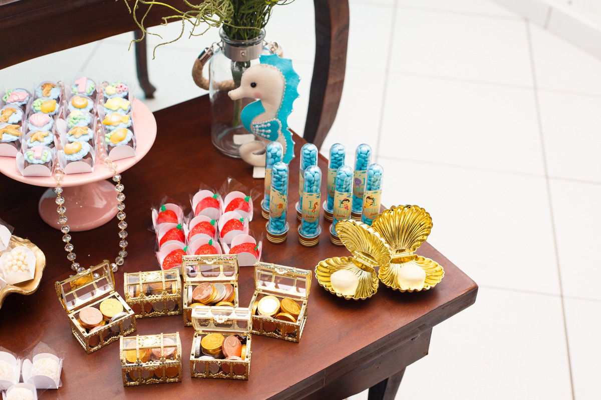 Detalhes da mesa do bolo de aniversário infantil no tema fundo do mar, com cavalo marinho, ostras com pérolas e baús de tesouro.