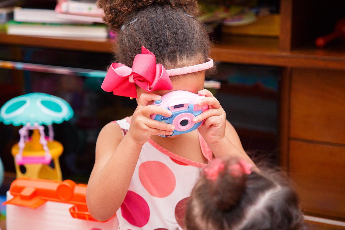 Criança com uma câmera de brinquedo tirando foto da irmã mais nova.