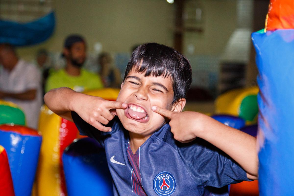 Criança brincando em brinquedão inflável e fazendo careta engraçada para a foto.