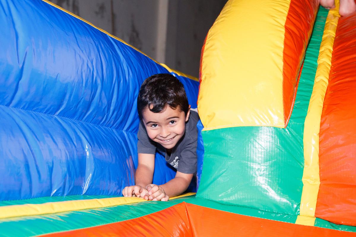 Criança brincando em brinquedão inflável e olhando para a câmera com cara de sapeca.