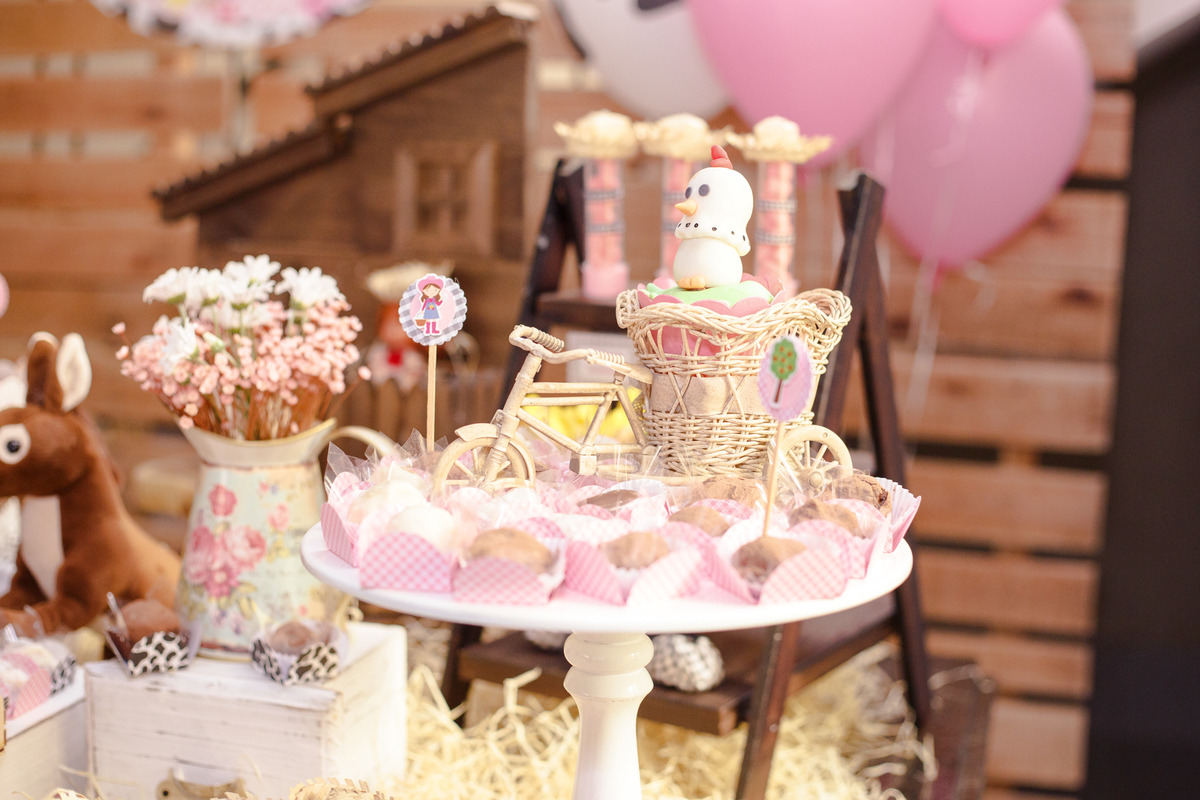 Detalhe da mesa do bolo de um aniversário infantil no tema fazendinha, com detalhe em uma galinha de biscuit e regadores de flores.