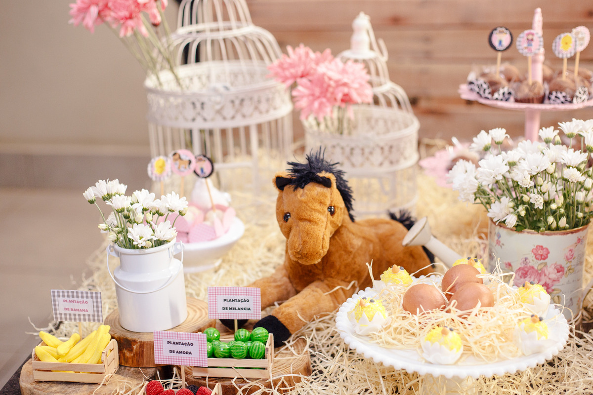 Detalhes da mesa do bolo de um aniversário infantil do tema fazendinha, com um cavalo de pelúcia, ovos e pintinhos e uma plantação de frutas.