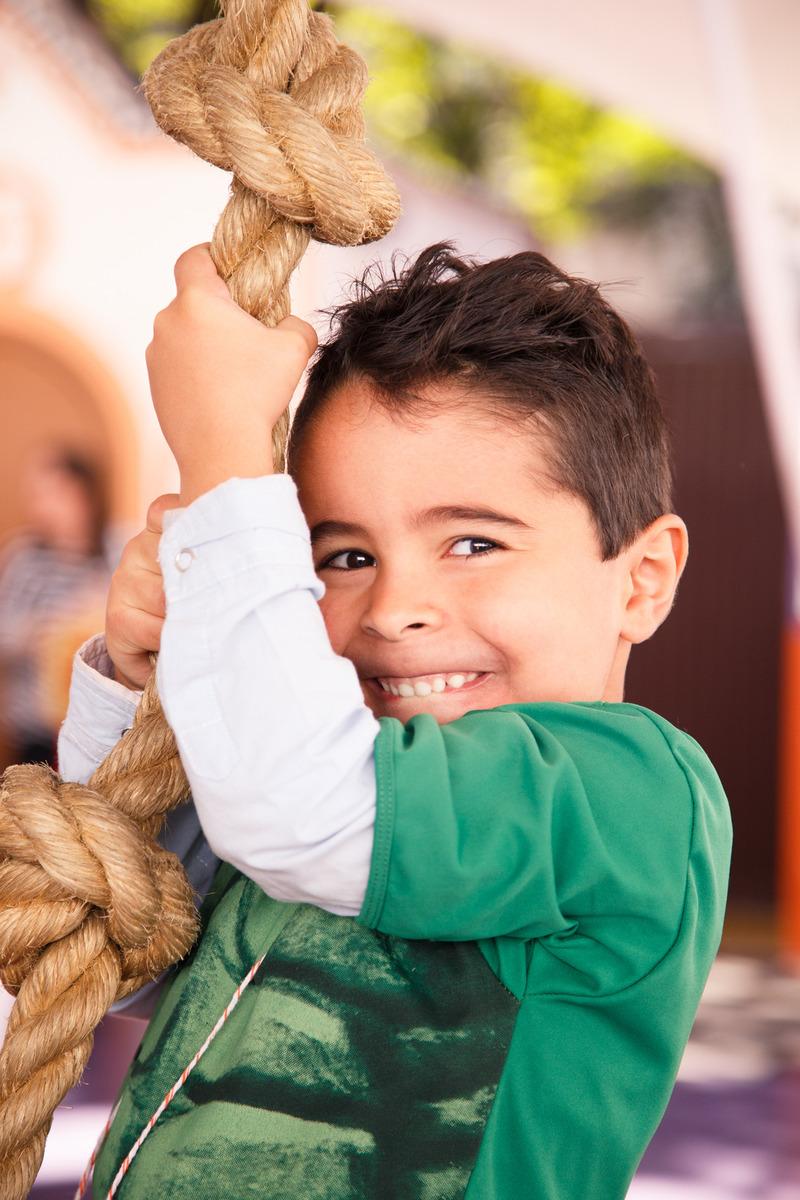 Criança pendurada em uma corda para escalar em seu aniversário infantil, fazendo uma careta engraçada para a foto.