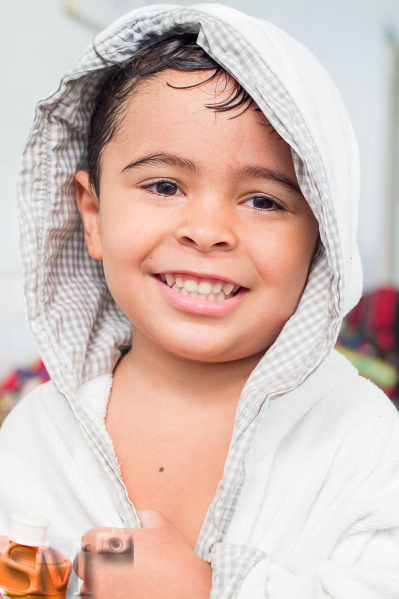 Criança molhada saindo da aula de natação enrolado em um roupão, olhando para a câmera e sorrindo.