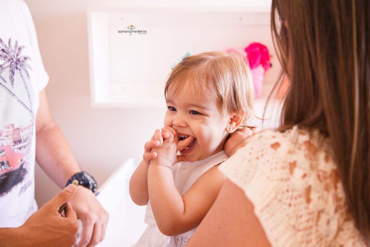 Criança de 1 ano com dentes nascendo e as mãos na boca para coçar a gengiva.