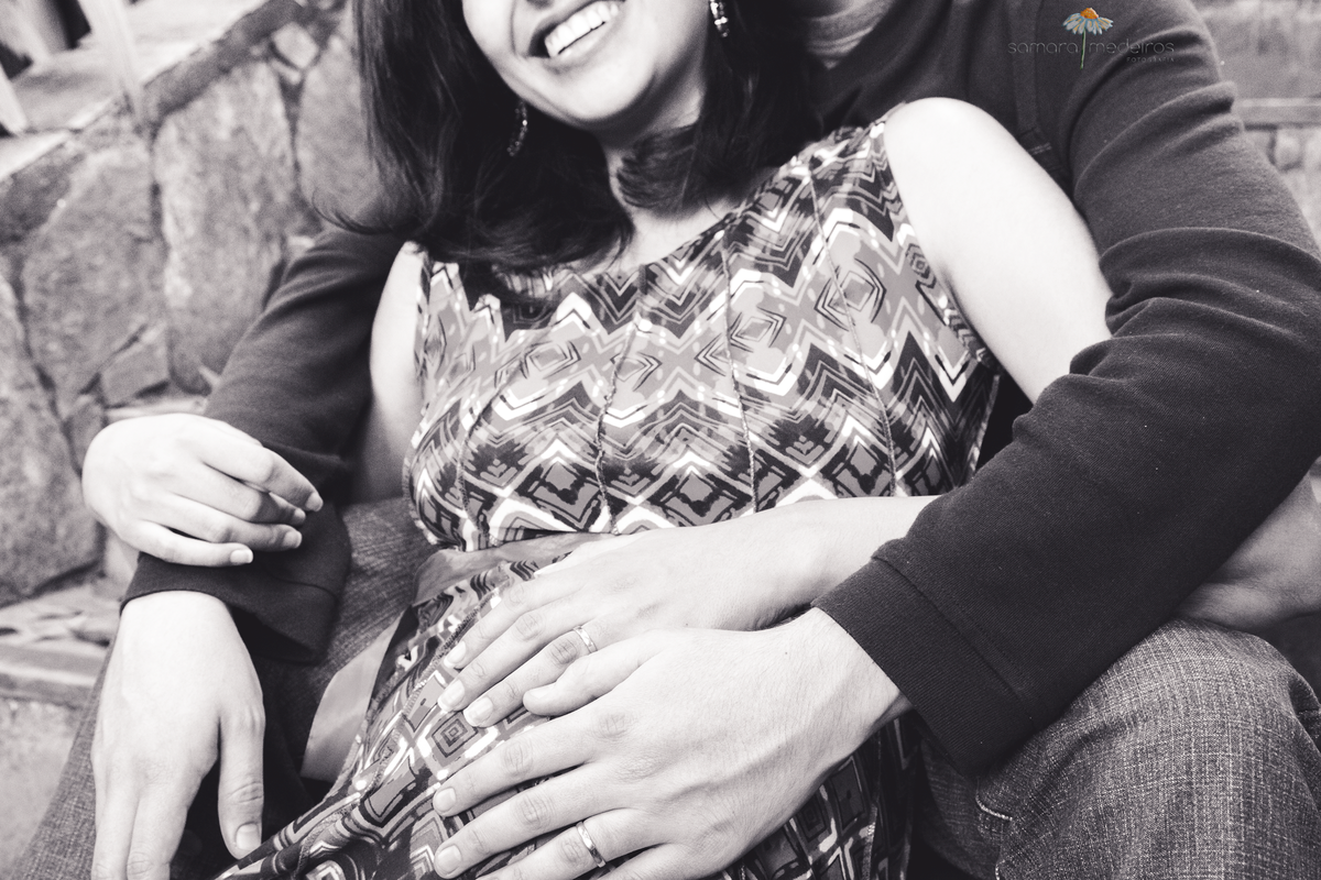 Casal sorrindo sentado em uma escada, ambos com a mão da barriga da mulher que está grávida.