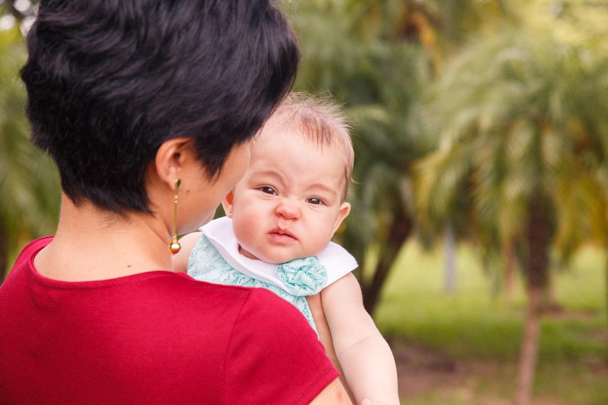 Mãe de costas com sua bebê no colo olhando por cima do ombro dela, para a câmera, fazendo uma careta.