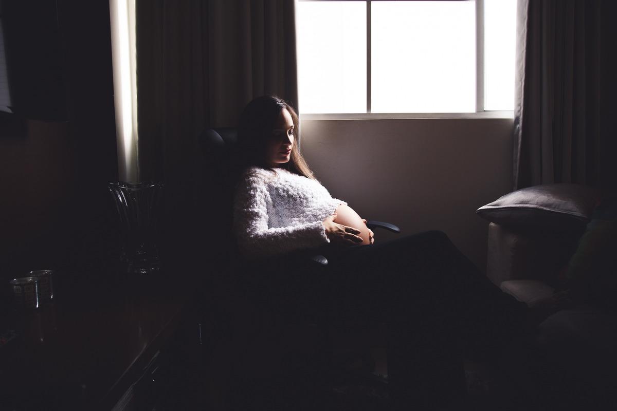 Gestante sentada em uma cadeira em sua casa, ao lado da janela, com sombras ao seu redor e a luz entrando pela janela e iluminando parcialmente seu rosto, tronco e barriga.