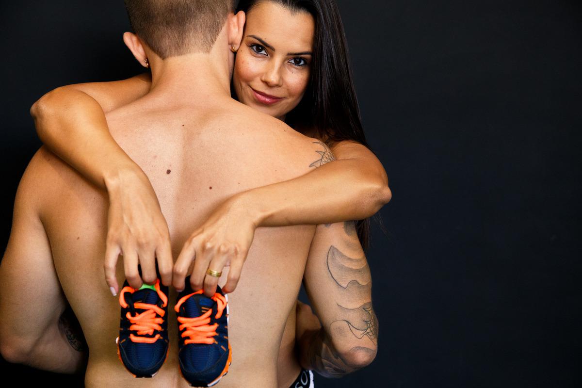 Gestante abraçando o marido, que está de costas para a foto, segurando um sapatinho do bebê que está para nascer.