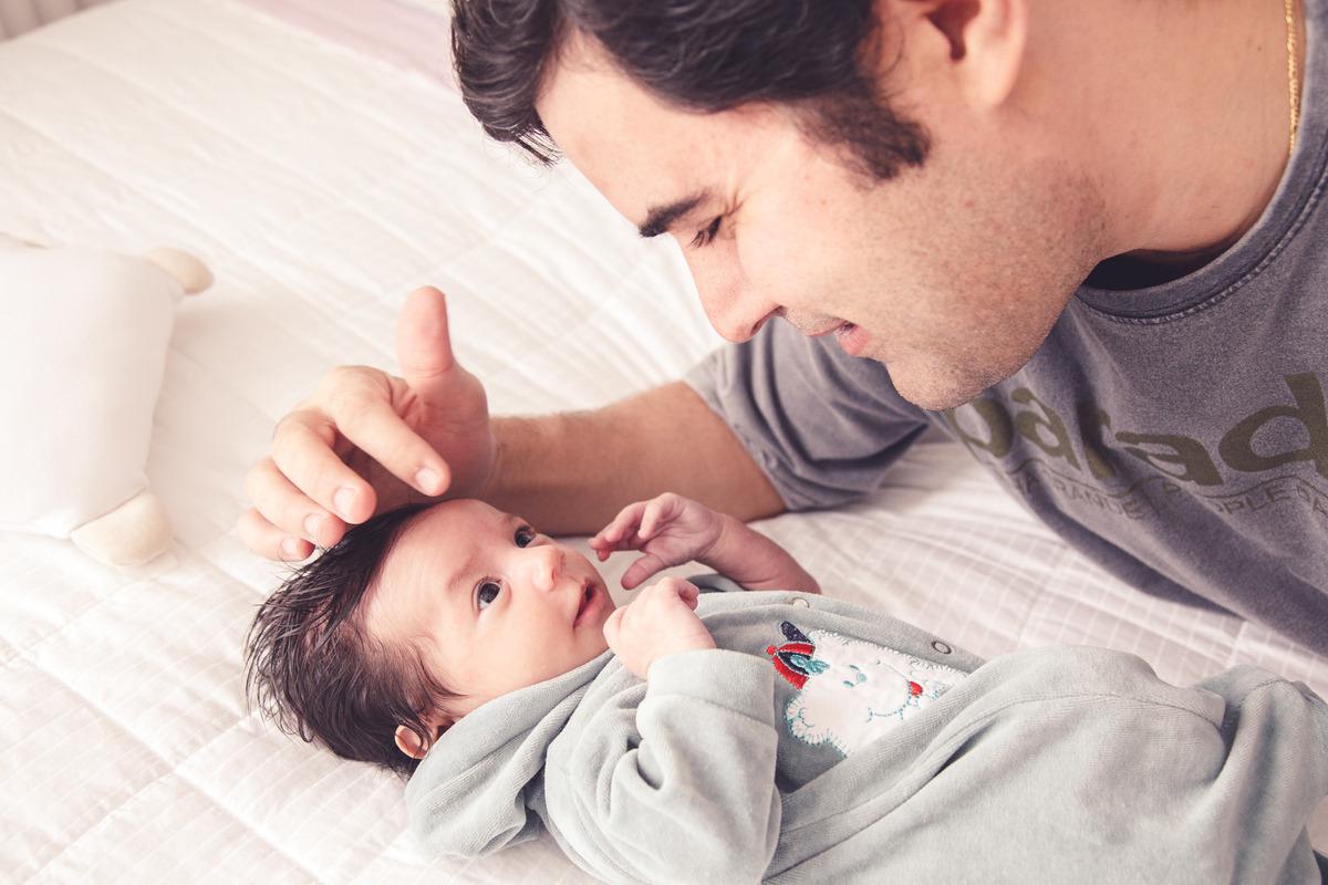 bebê deitado na cama com seu pai observando-o e fazendo carinho na cabeça