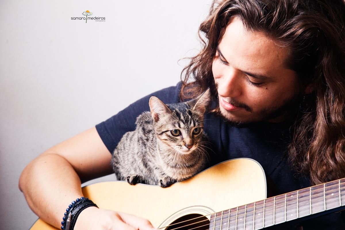 Homem tocando violão olhando para sua gatinha que está sentada em cima do mesmo violão.