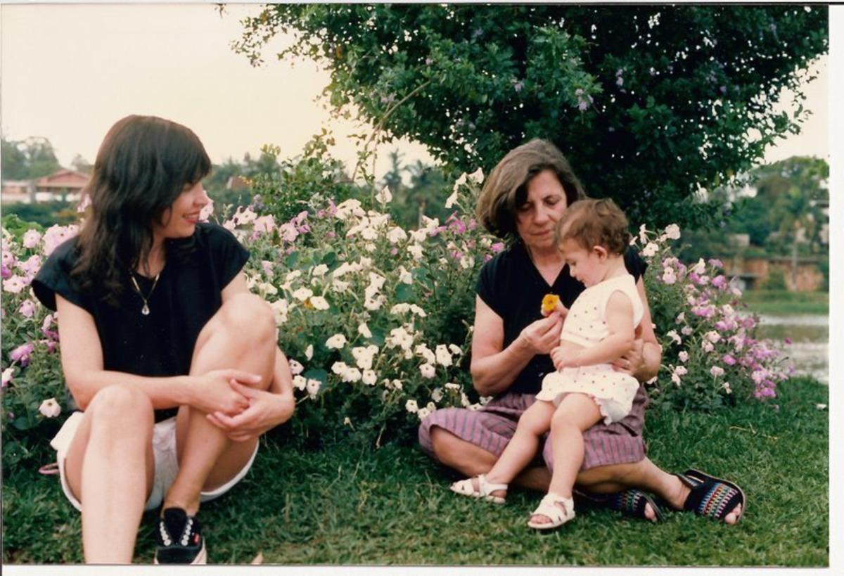 Foto antiga escaneada de uma família sentada na grama com flores atrás, mãe, filha e neta.