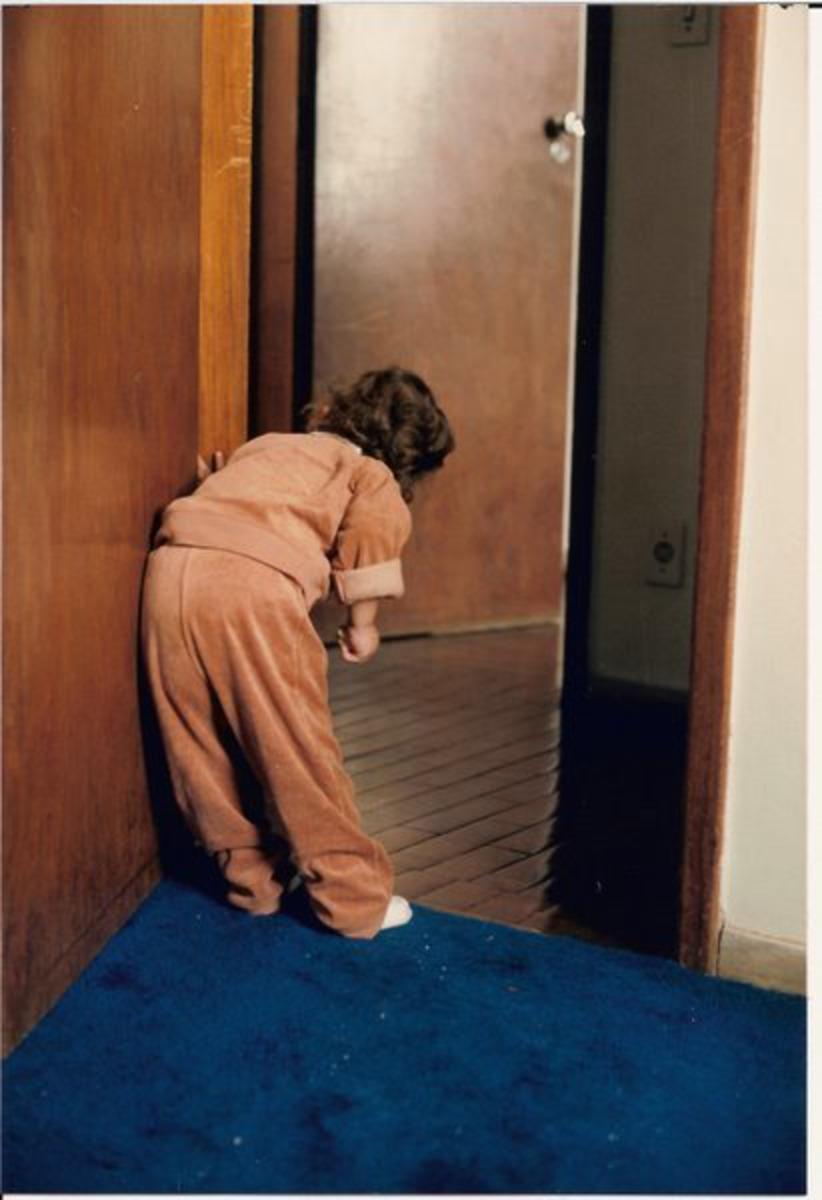 Foto antiga escaneada de uma criança de roupinha marrom espiando pela porta do quarto.