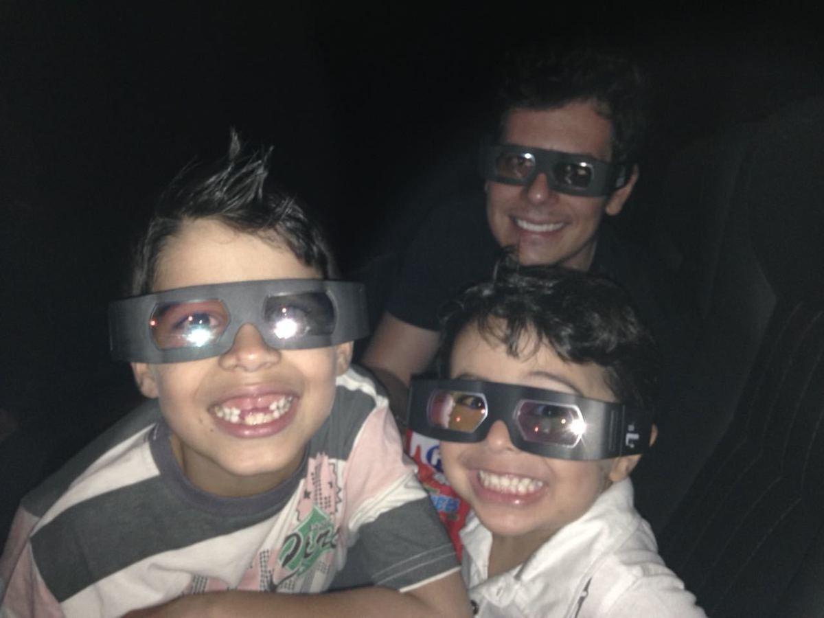 Duas crianças em primeiro plano usando óculos 3D e um adulto ao fundo.
