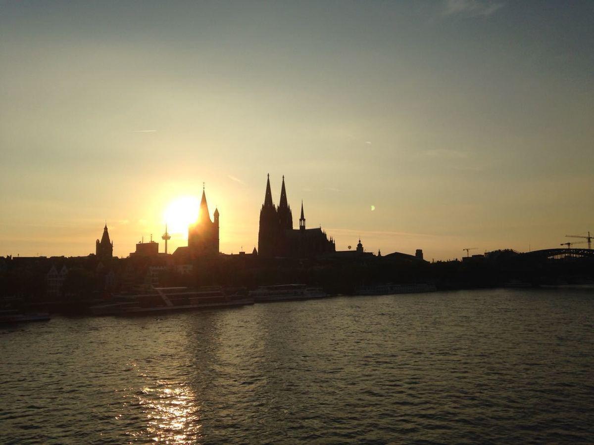 Por do sol com um castelo em silhueta e o sol atrás do castelo, com uma vista para um canal