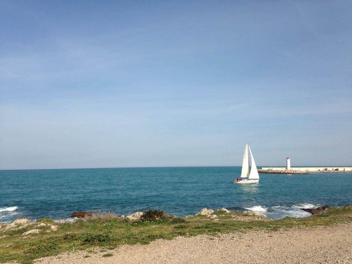 Paisagem com vista para o mar com um barco a velas