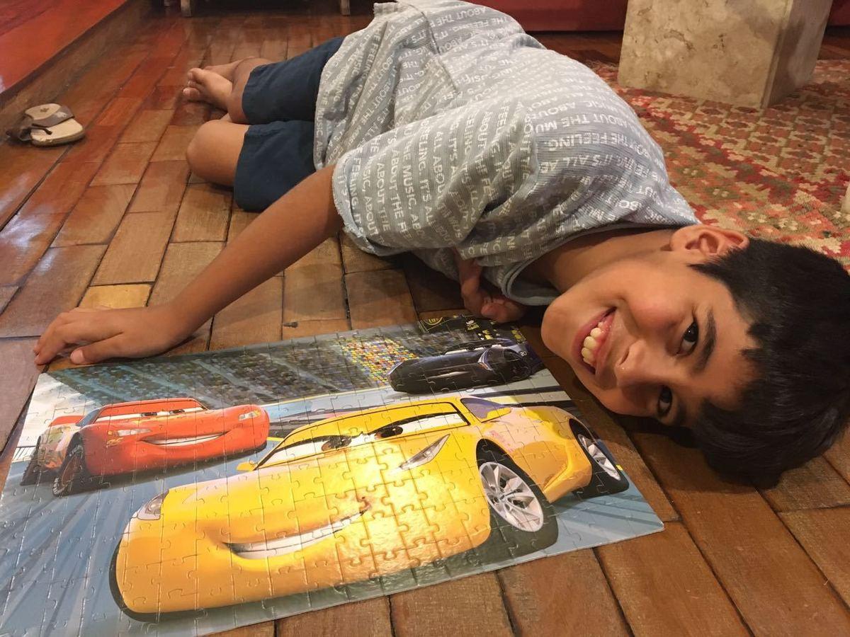 Criança deitada no chão posando ao lado de um quebra cabeças