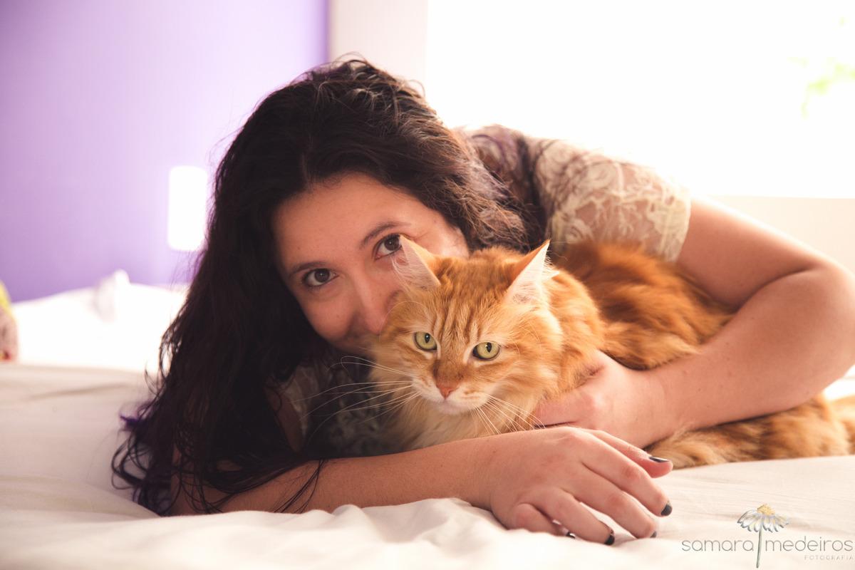 Fotógrafa deitada na cama abraçando um gato amarelo peludo. Ambos olham para a foto.
