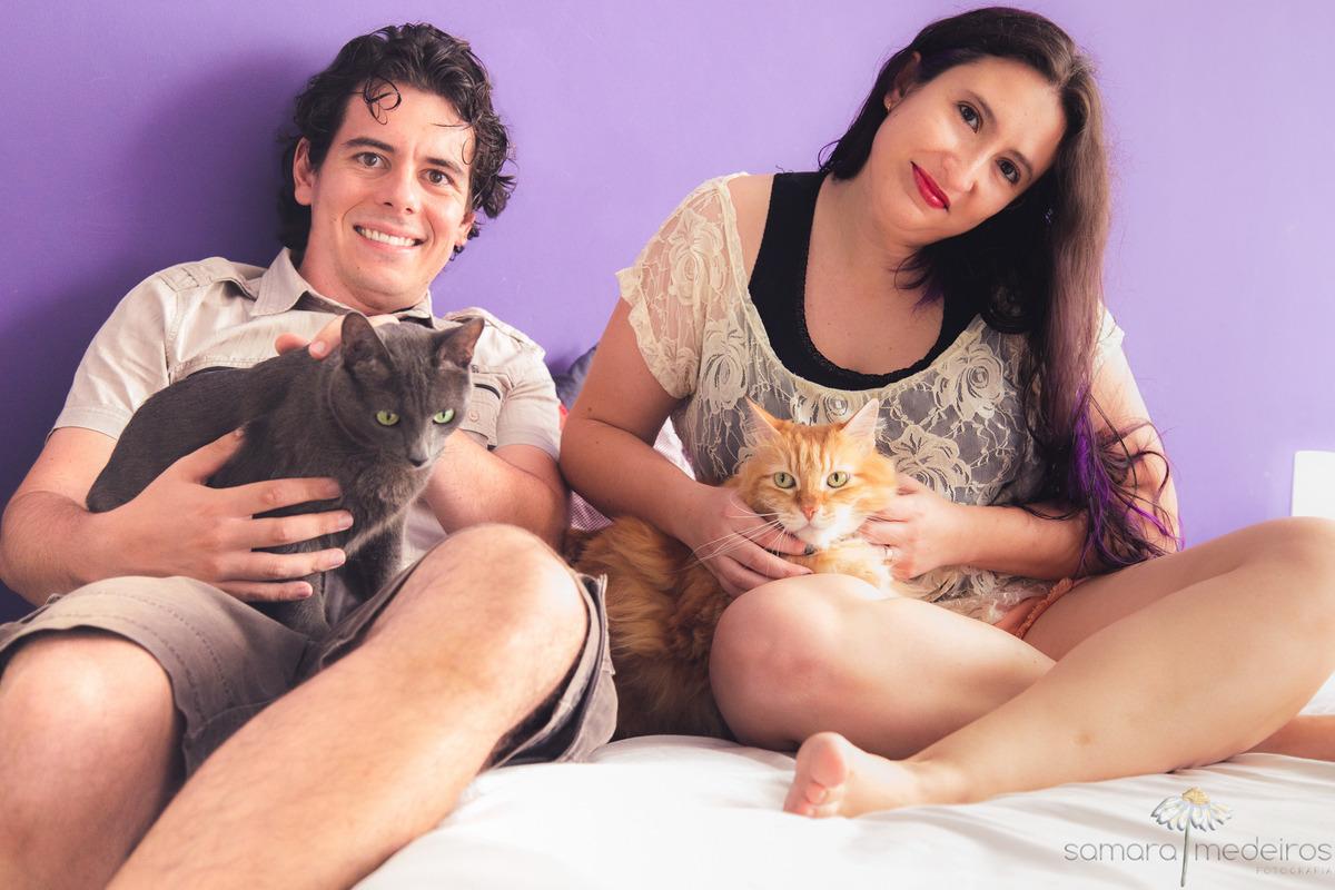 Foto em família de um casal e dois gatos, um cinza no colo do rapaz e um amarelo no colo da moça, todos sentados na cama com um fundo de parede roxa.