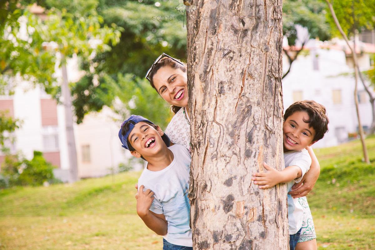 Mãe e seus dois filhos brincando durante um ensaio fotográfico, atrás do tronco de uma árvore, todos sorrindo.