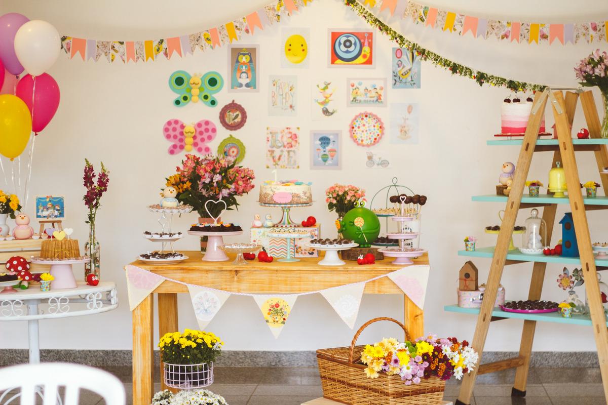 Mesa do bolo de aniversário infantil no tema jardim.
