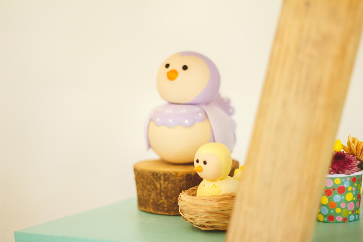 Detalhe da decoração de aniversário infantil no tema jardim, com um passarinho e seu filhote de biscuit.