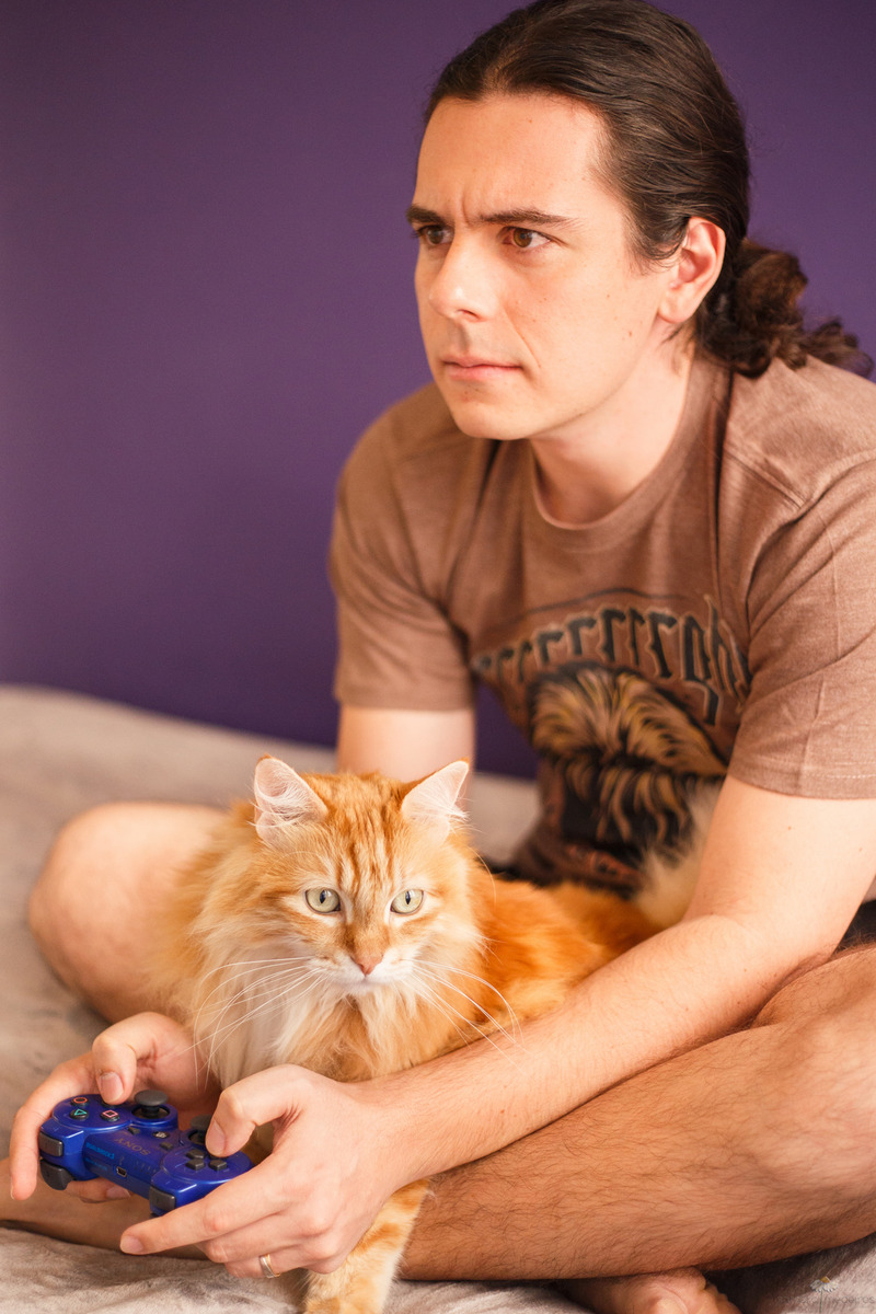 Homem sentado de pernas cruzadas com uma manete de video game na mão e um gato amarelo peludo no colo.