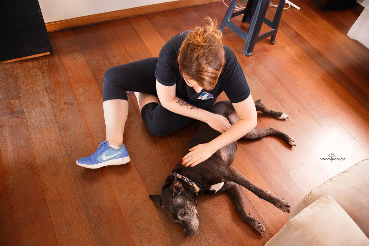Pet sitter sentada no chão fazendo carinho no pitbull do qual foi cuidar.