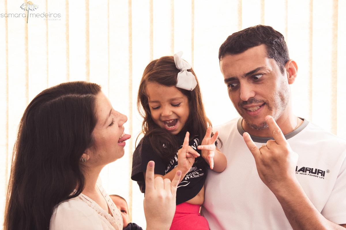 Pais e filha brincando em casa, fazendo com as mãos o símbolo do heavy metal e rindo.