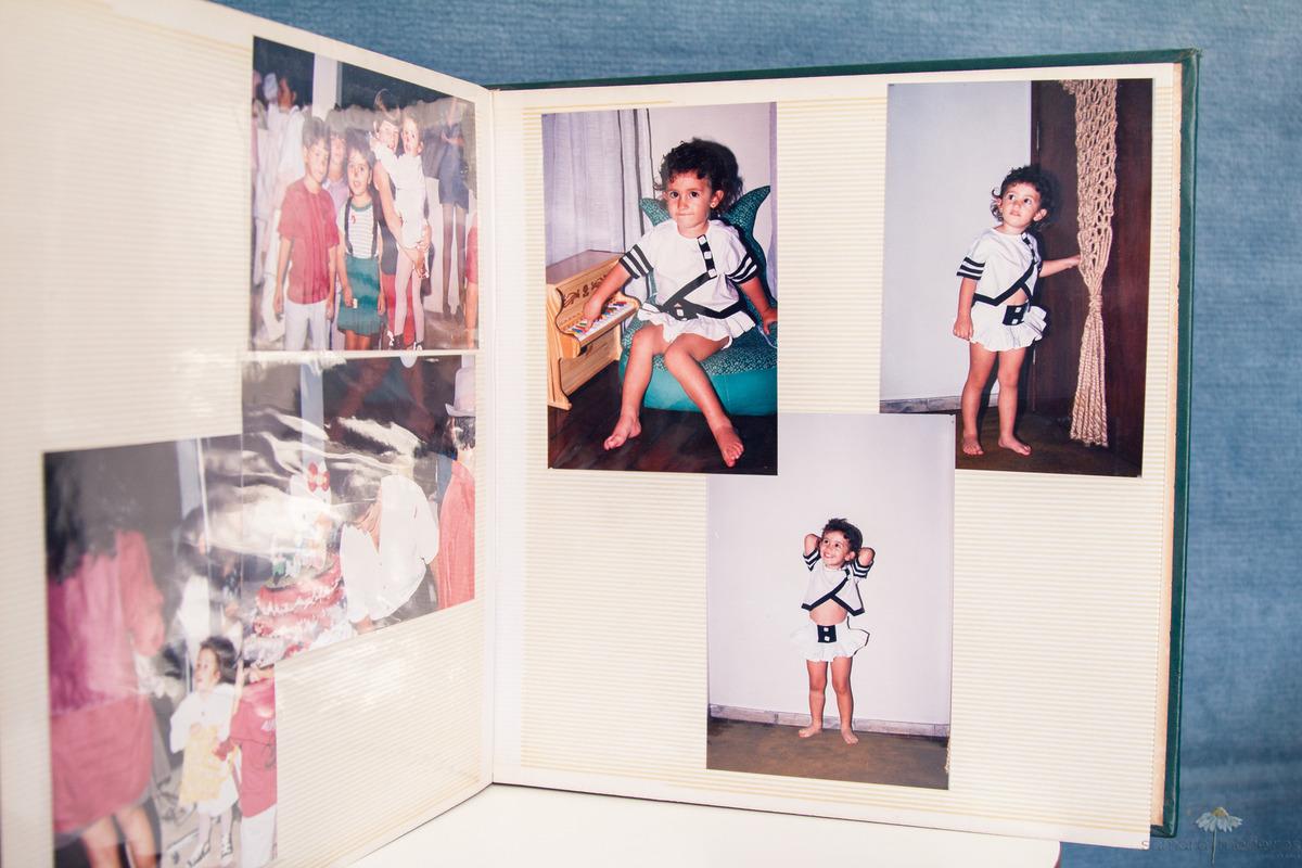 Foto de um album de fotos antigo, com fotografias reveladas de criança.