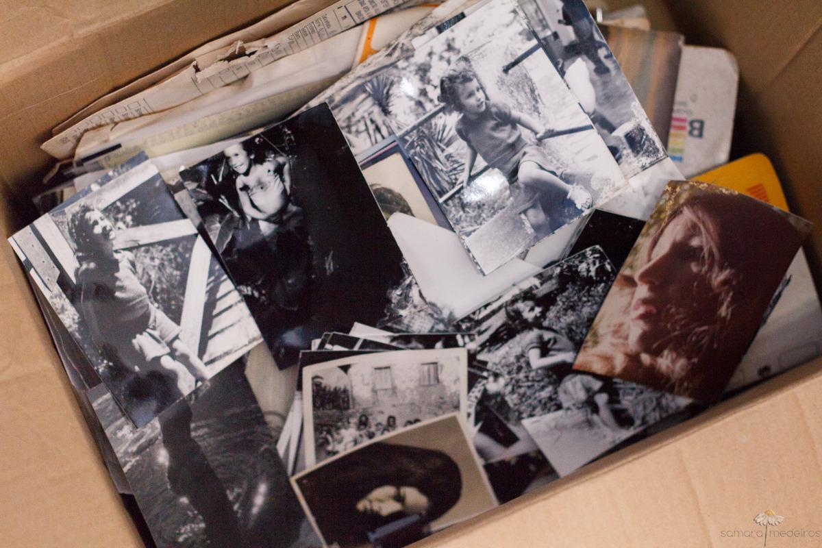 Caixa de papel cheia de fotos antigas reveladas.