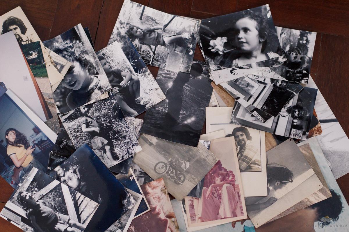 Várias fotos antigas reveladas espalhadas pelo chão.