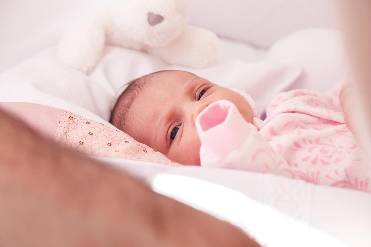 Bebê recém nascida deitada em seu berço olhando para a câmera.
