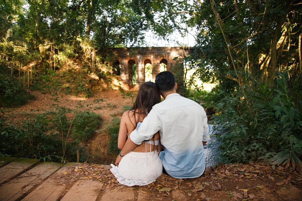 Casal sentado em uma ponte olhando para ruínas de um trilho de trem, de costas para a foto.